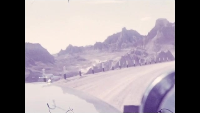 1930s: View from inside car that drives on a road surrounded by rock formations and spires.