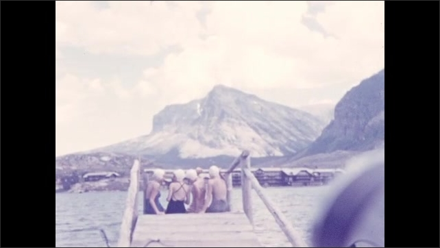 1930s: UNITED STATES: people sit on jetty. Building by road. Swimmers on jetty.
