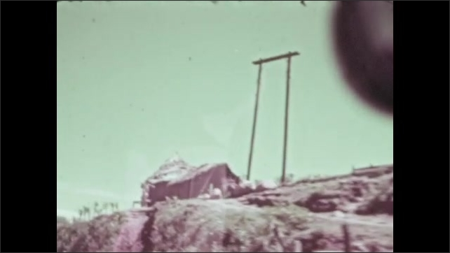 1930s: Car drives down road.  Farm on hill.  Person stands in front of barn.
