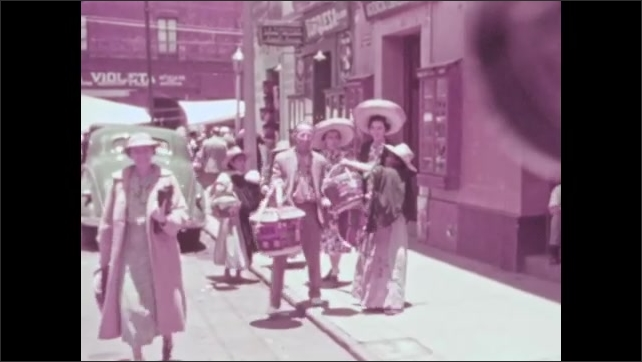 1930s: man carries basket and walks down sidewalk near car as women wear sombreros, salesman in overalls plays with ball and cup toy and ladies sell handicrafts outside downtown stores in Mexico.