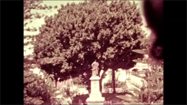 1930s: trees and bushes grow around a statue in a walled garden with building with two story balcony.  car parks in front of apartment building in village in Mexico.