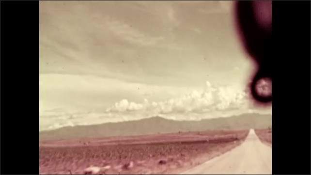 1930s: highway stretches across plain toward mountain range and  around curvy hilly cliff as clouds float in distance.