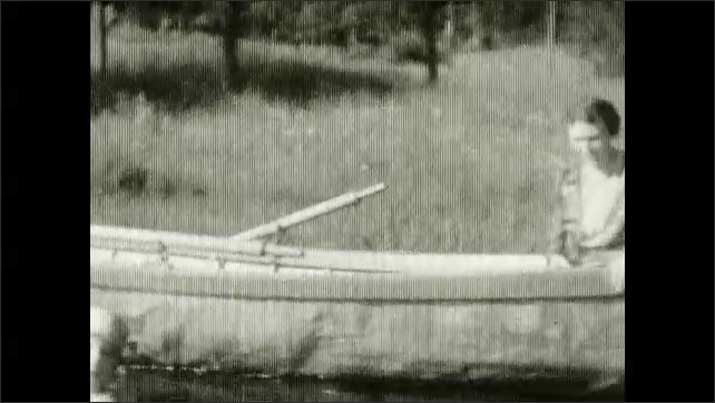 1920s: Man swims. Girl pretends to swim, she stands in the water, woman watches her from boat. Girl dries herself. Woman watches the girl who plays with the water from boat.