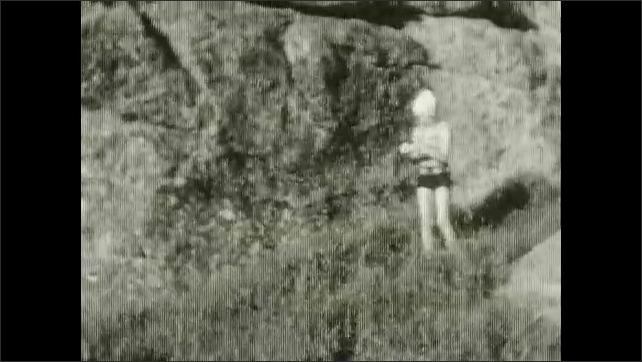 1920s: Rocks with trees in the background. Lake with rocks. A girl stands and poses in front of rocks. A swan swims in a lake.