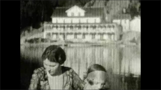 1920s: A woman and a girl who holds a doll sit on a boat in a lake, a big building and rocks in the background. Face of girl and woman, they talk. Blurred building.