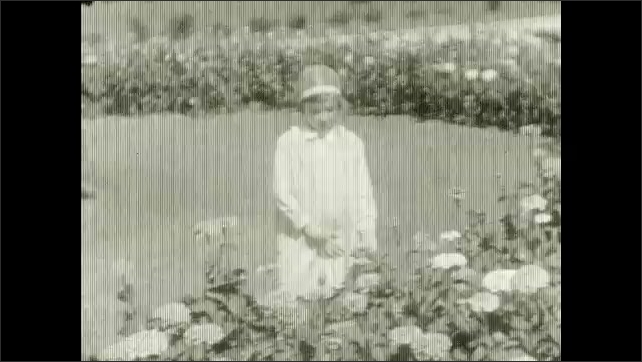 1920s: UNITED STATES: girl in gardens. Girl stands by flowers. View of building through gardens. Girl in meadow