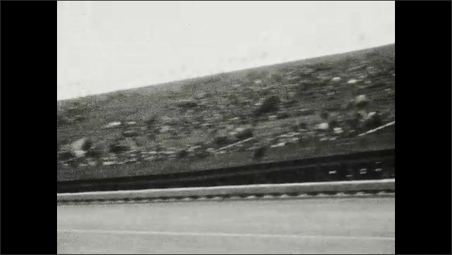 1920s: UNITED STATES: crashed car on race track. Man walks near crashed car. Spectators in race stands