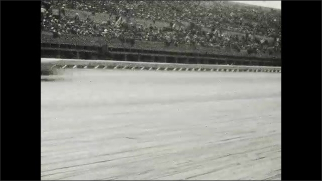 1920s: UNITED STATES: Number 2 racing car. Mechanic changes wheel on car. Cars on race track.
