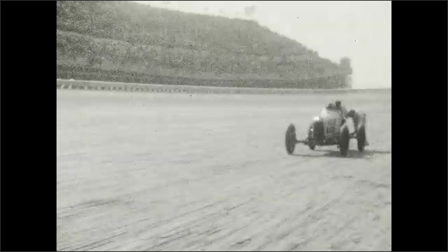 1920s: UNITED STATES: cars race past stands at track. Men push car. Driver in car.