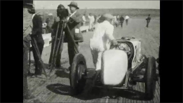 1920s: UNITED STATES: racing driver in car. Drivers shake hands. Man pushes car. Steering wheel in racing car. Ladies in cabin.