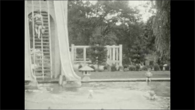 1920s: UNITED STATES: outdoor pool and slides. Lady carries bucket of water up ladder.