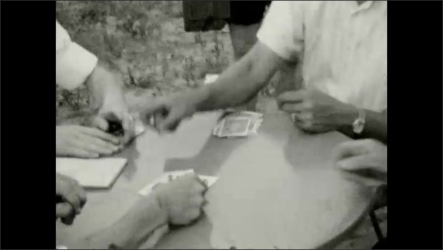1920s: UNITED STATES: man plays cards at outdoor table. Man smiles. Man smokes pipe by house