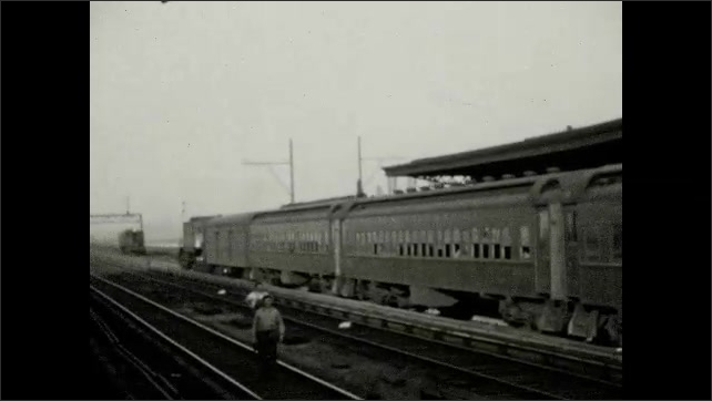 1920s: UNITED STATES: guard on platform of railway station. View of tracks from train. Train pulls out of station.