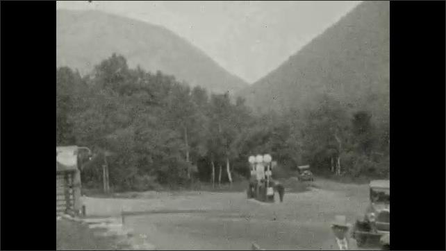 1920s: UNITED STATES: 1826 landslide sign. Bridge across river. Cars in car park. Man by car.