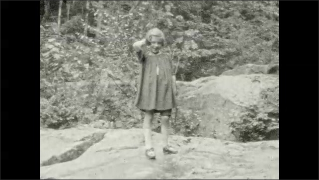 1920s: UNITED STATES: ladies stand near waterfall. Girl waves at camera. Girl climbs over rocks by waterfall