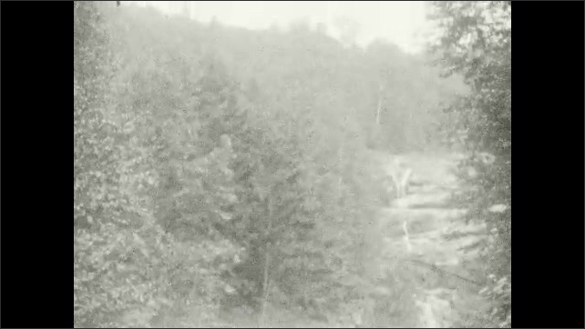 1920s: UNITED STATES: child walks near waterfall. Man waves at camera from rocks. Girl waves at camera. Child climbs over rocks