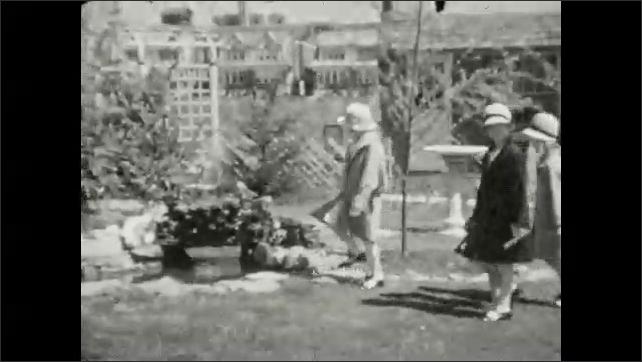 1920s: UNITED STATES: ladies walk with girls in garden. Girls walk towards camera.