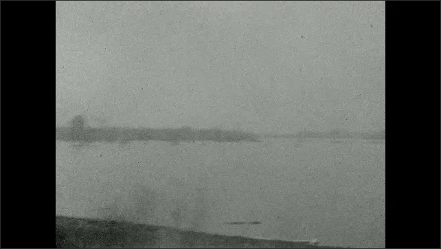 1920s: UNITED STATES: view along road from car. Car crosses bridge. Pylons by road. Animals in field. Flooded landscape.