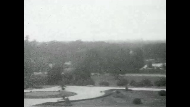1920s: UNITED STATES: deer by camera. View across zoo and park. Benches in park gardens. Girl walks with mother