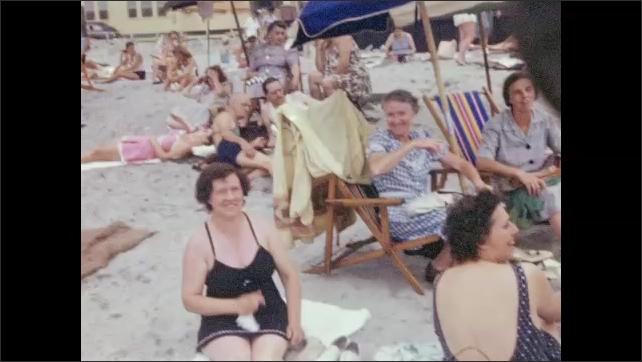 1940s: Women sit on beach talking. Man talks to women.