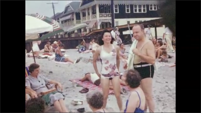 1940s: Men and women sit in group on beach, talking. Woman stands next to man and they pose. Different man poses with same woman.