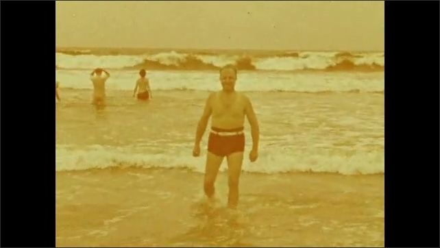 1940s: Two women on beach, talking, smiling. People on beach. Man walking into water, turns around, then dives into water. Dog on beach. Dog being pet.