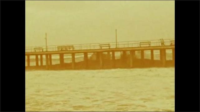 1940s: Waves crashing under boardwalk along beach. People run on boardwalk. Woman stands in wind, smiling.