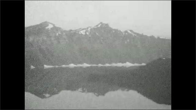 1940s: Mountainside surrounding lake. Person sits on edge of cliff above lake.