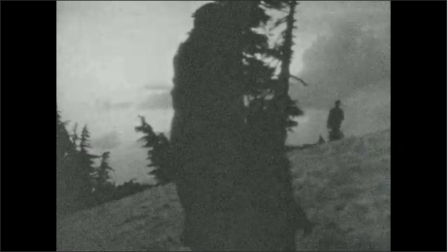 1940s: Looking out over horizon. Two people on side of mountain trail in silhouette.