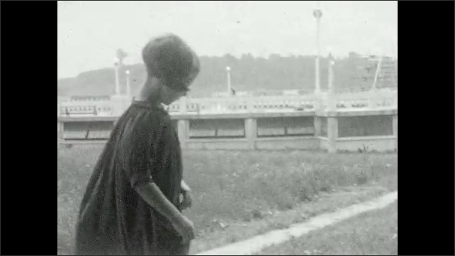 1920s: Girl looks in mirror, smiles. Woman looks in mirror, smiles. Girl stands in front of building, poses, waves, walks up hill.