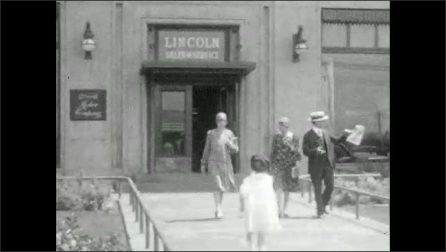 1920s: Cars drive drown street. City. Family walks down sidewalk. Woman locks car door. People cross the street.