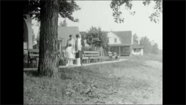 1920s: People walk down sidewalk. Man, women, and child walk along sidewalk, stop under large tree. Man jumps out from behind tree.