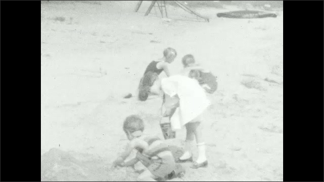 1920s: People sit on benches. Kids play in the sand by the water.