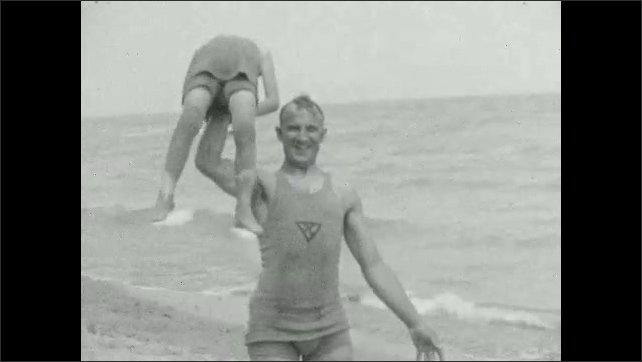 1920s: Men walk down sidewalk. Man on beach picks up girl, raises her up and down with one hand, carries girl into water.
