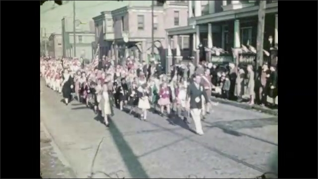 1930s: Women in uniform play instruments and march in parade. People of all ages carry flags and walk in parade. Uniformed marching band walks in parade.