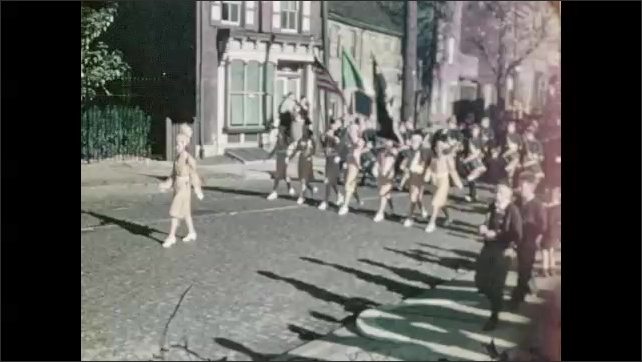 1930s: Boy walks down street. Men in uniform walk along parade route. Marching band carries flags and instruments on parade route.