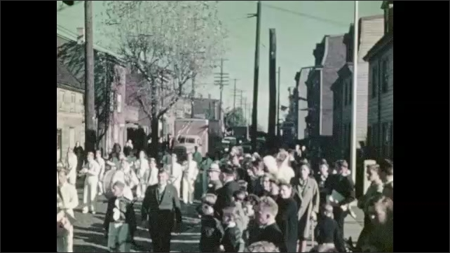 1930s: Women and men in uniform carry flags and play instruments in marching band. Cars and trucks draped in streamers drive in parade.