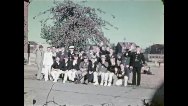 1930s: Cars and trucks drive down parade route. Men in uniform pose in park. Men wave and pose for photos in park.