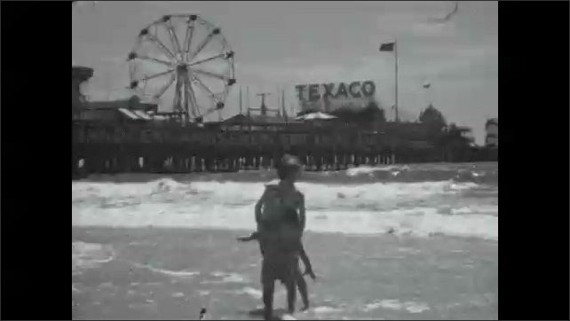 1920s: Girl and baby standing in ocean on beach. People walking on beach with baby, girl crawling in sand.
