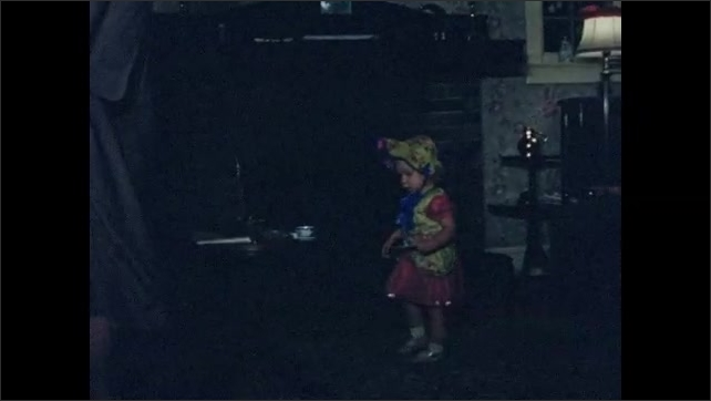 1950s: UNITED STATES: toddler in fancy dress. Girl spins around in costume.