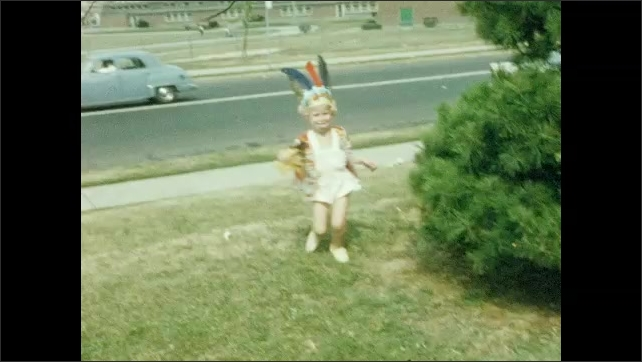1950s: UNITED STATES: girl in garden. Girl with doll, Girl in fancy dress. Girl dressed as Indian