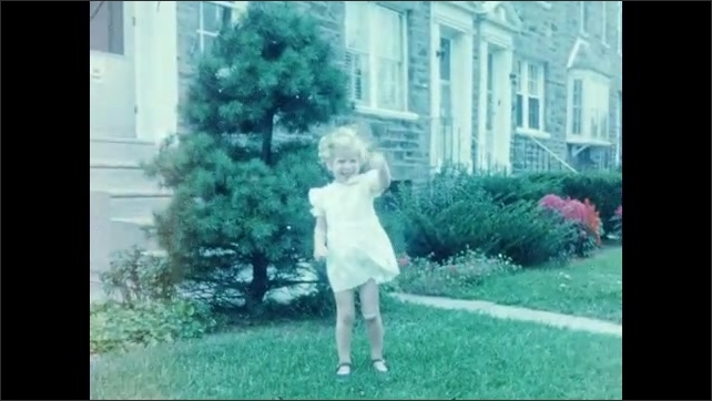1950s: UNITED STATES: exterior of house. Girl runs on grass. Girl waves at camera. Girl stands by tree. Girl in costume