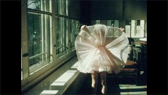 1950s: Children in costumes dance.  Little girl looks through skirt.  Girl dances.