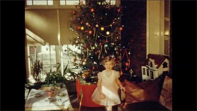 1950s: Little girl watches train move around Christmas tree.  Girl walks around room.