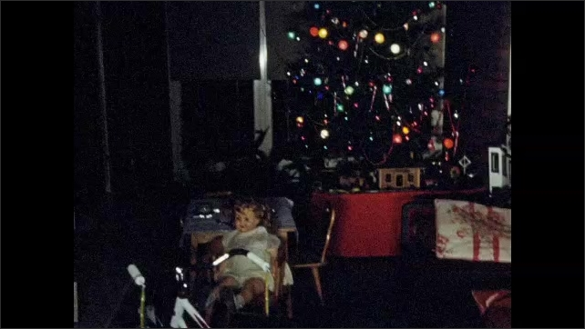 1950s: UNITED STATES: train underneath Christmas tree, Lights on tree. Children sit at table by tree. Doll on table. Bike by tree