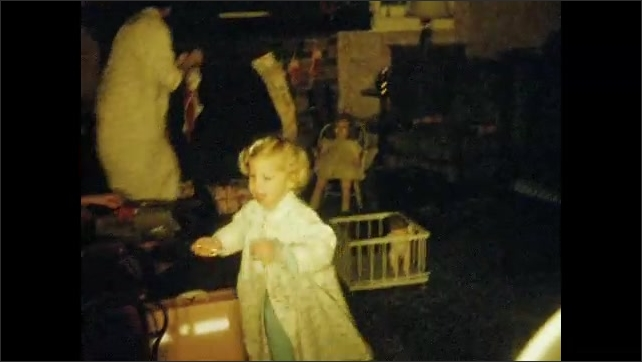 1950s: UNITED STATES: girl opens Christmas presents. Girl shows presents to camera. Girls in dresses. Children dance at party. Family gathering for Christmas