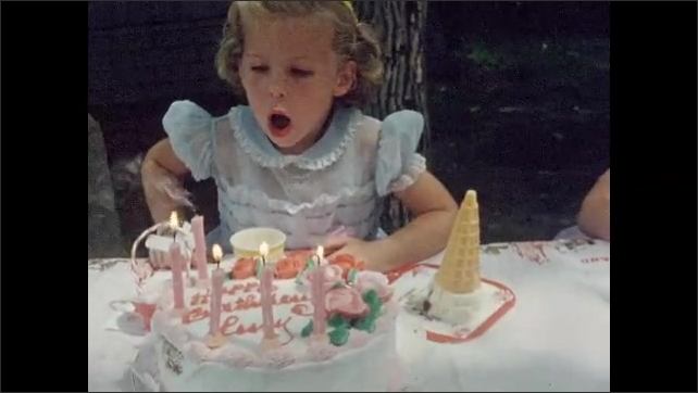 1960s: UNITED STATES: Happy Birthday Lucy cake. Birthday cake with rose decorations. Girl opens birthday presents in garden. Girl blows out candles on cake. Children eat clown shaped ice creams
