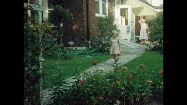 1960s: UNITED STATES: children hold hands and dance in circle at party. Girls fight at party. Girls walk along garden path. Ladies walk with children. Lady carries camera