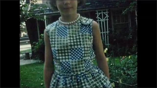 1960s: UNITED STATES: child walks in garden. Girl in dress and pearls. Child walks towards camera. Girls walk through garden. Lady walks along garden path