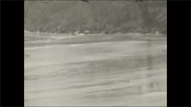1920s: UNITED STATES: girl sits on boat. View across roof tops. View across beach and shore. Trees by water.